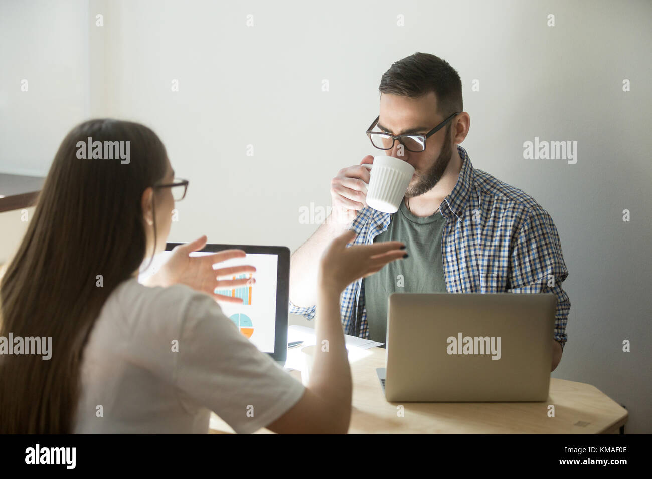Business meeting of millennial employees. Beautiful businesswoman in glasses explains to coworker concept of job. - Stock Image