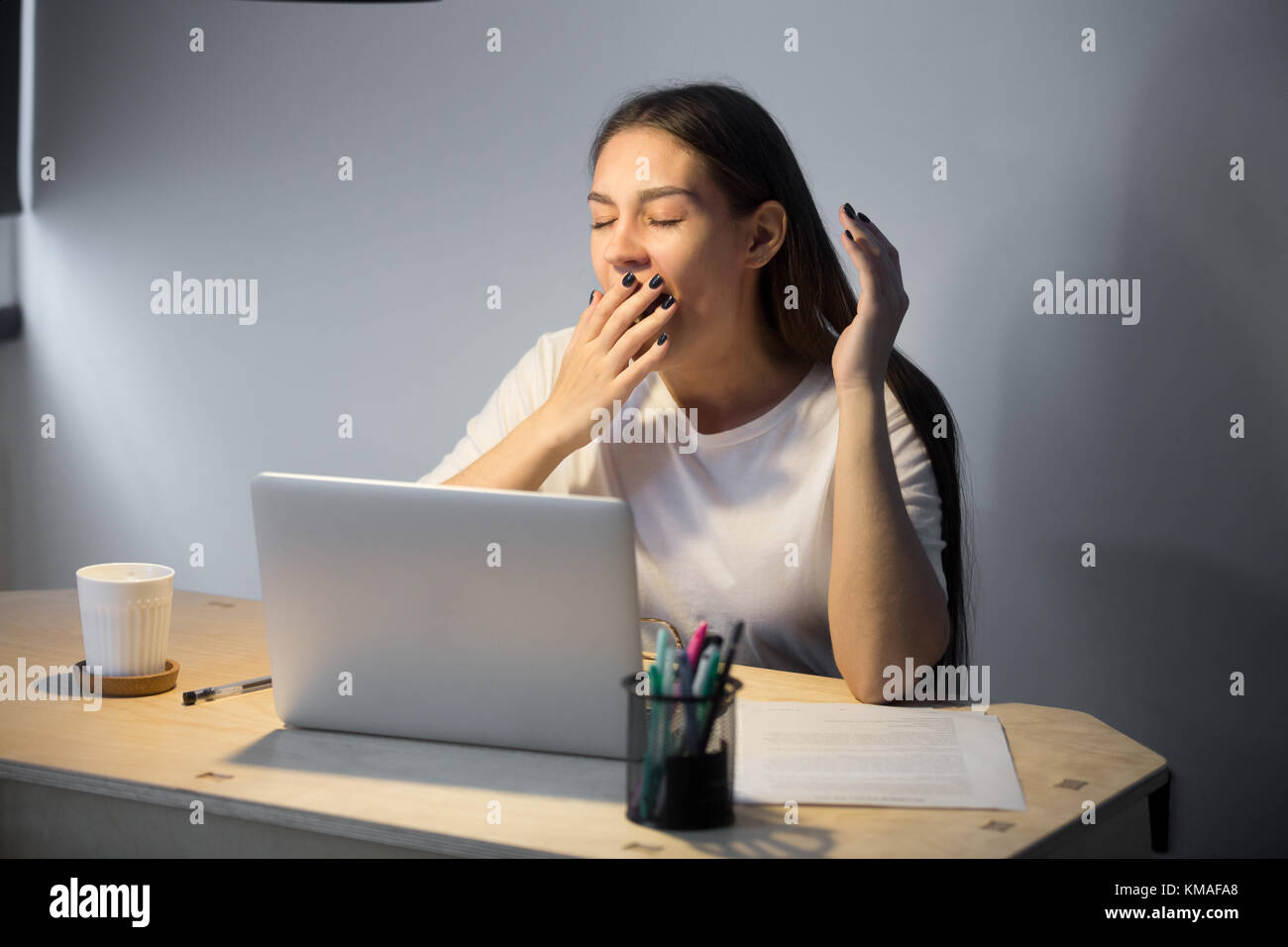 Exhausted millennial businesswoman in casual wear yawning at workplace in home office. Fatigued young female employer - Stock Image