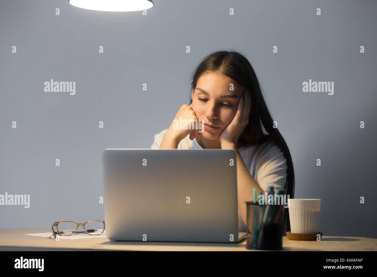 Tired businesswoman dozing leaning her head on hand on desk. Sleepy female manager suffering from lack of sleep. - Stock Image