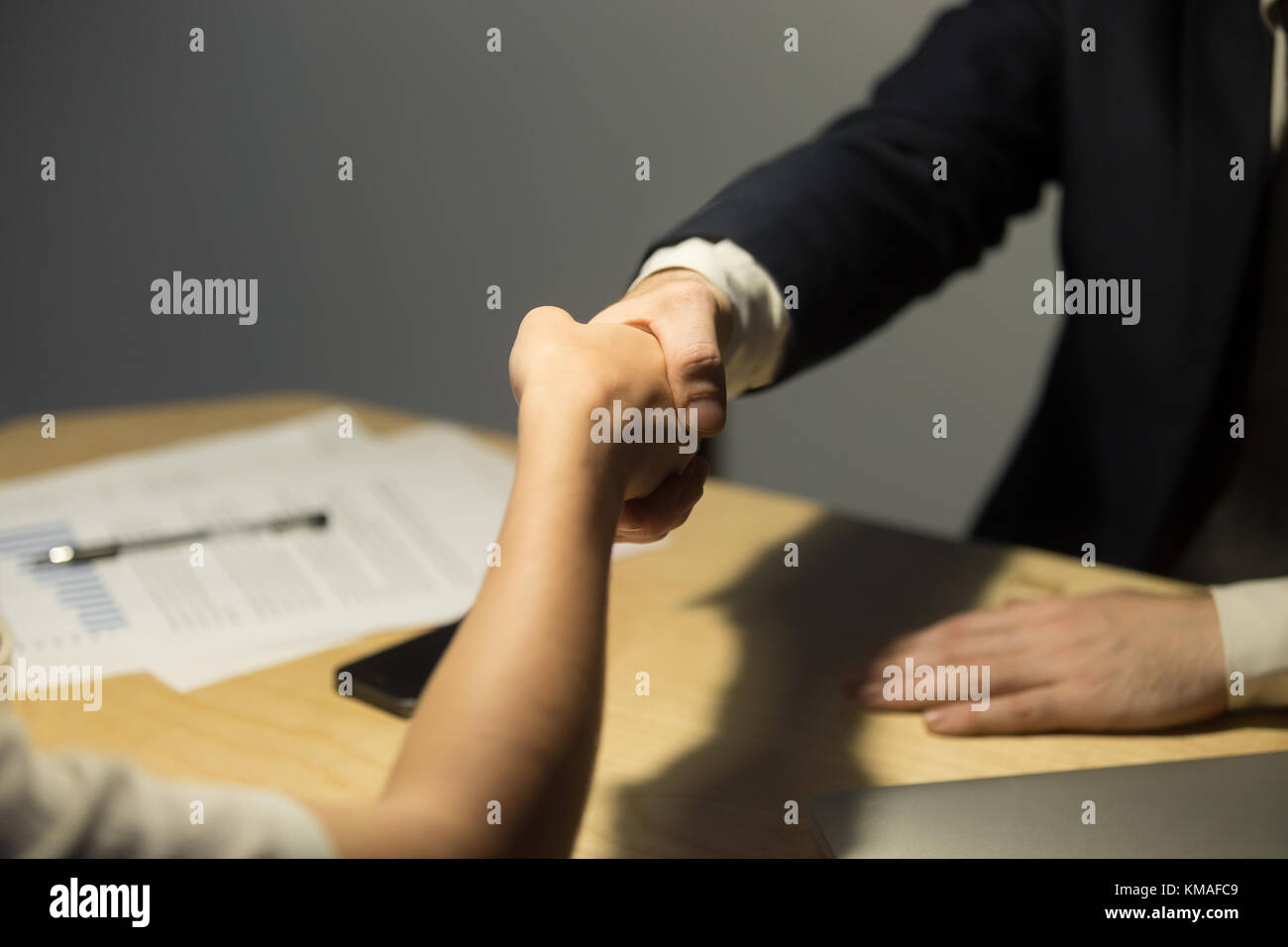 Businessman in suit greeting female coworker over desk in office after negotiations. Businesspeople reaching an Stock Photo