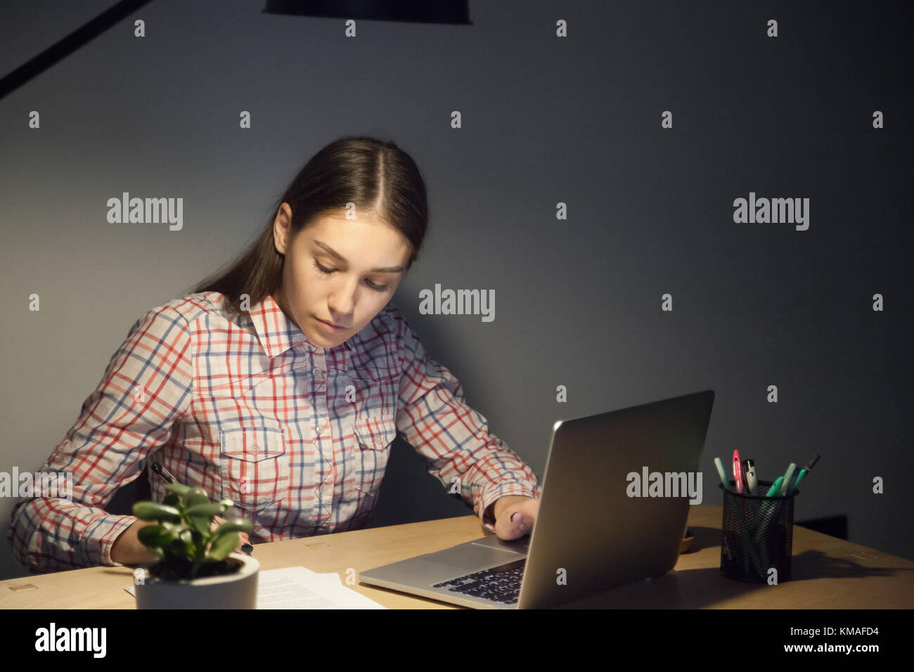 Millennial businesswoman in casual shirt working on laptop in office at night shift. Concentrated female worker Stock Photo