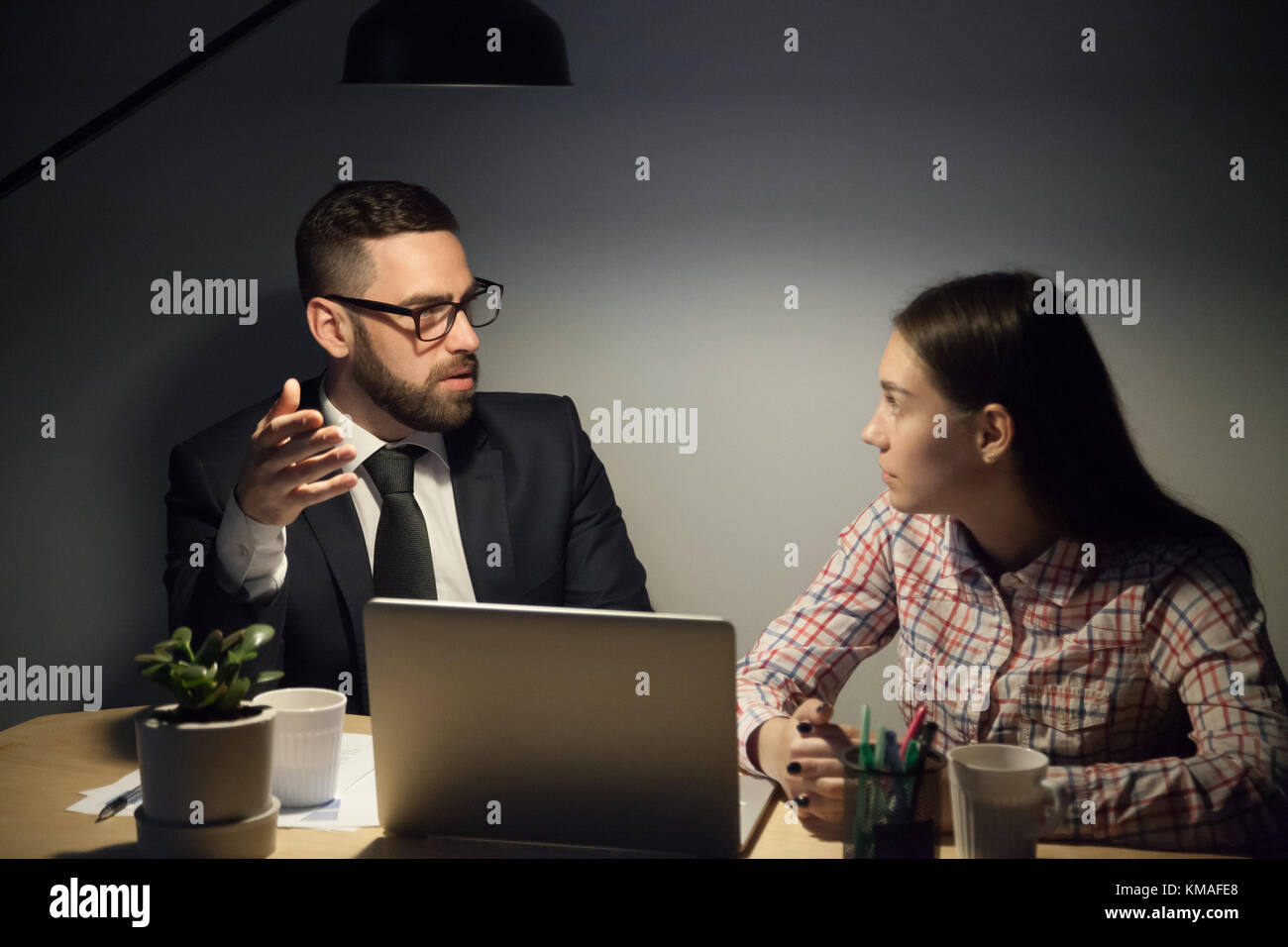 Bearded mentor in glasses and suit explaining young female worker hard urgent problems in job. Working to deadline - Stock Image