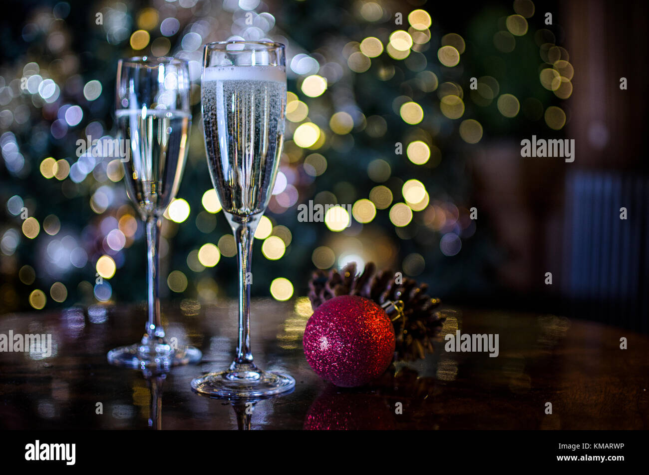 Two Champagne Glasses surrounded by Christmas Decorations - Stock Image