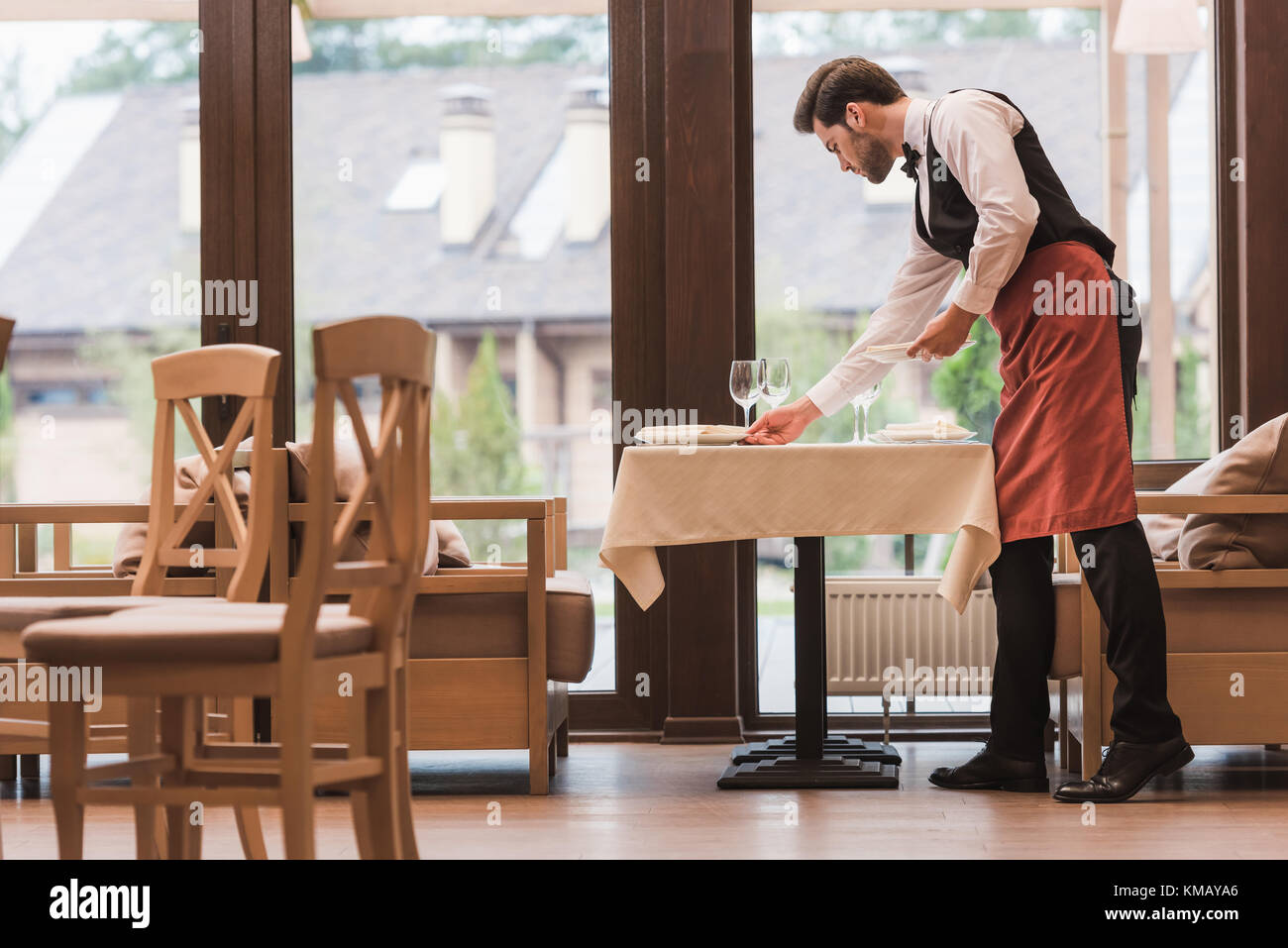 Waiter serving plates on table - Stock Image