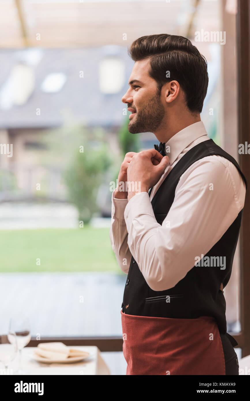 waiter fixing bow tie - Stock Image