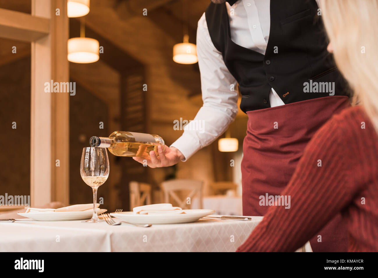 Waiter pouring wine into glass - Stock Image