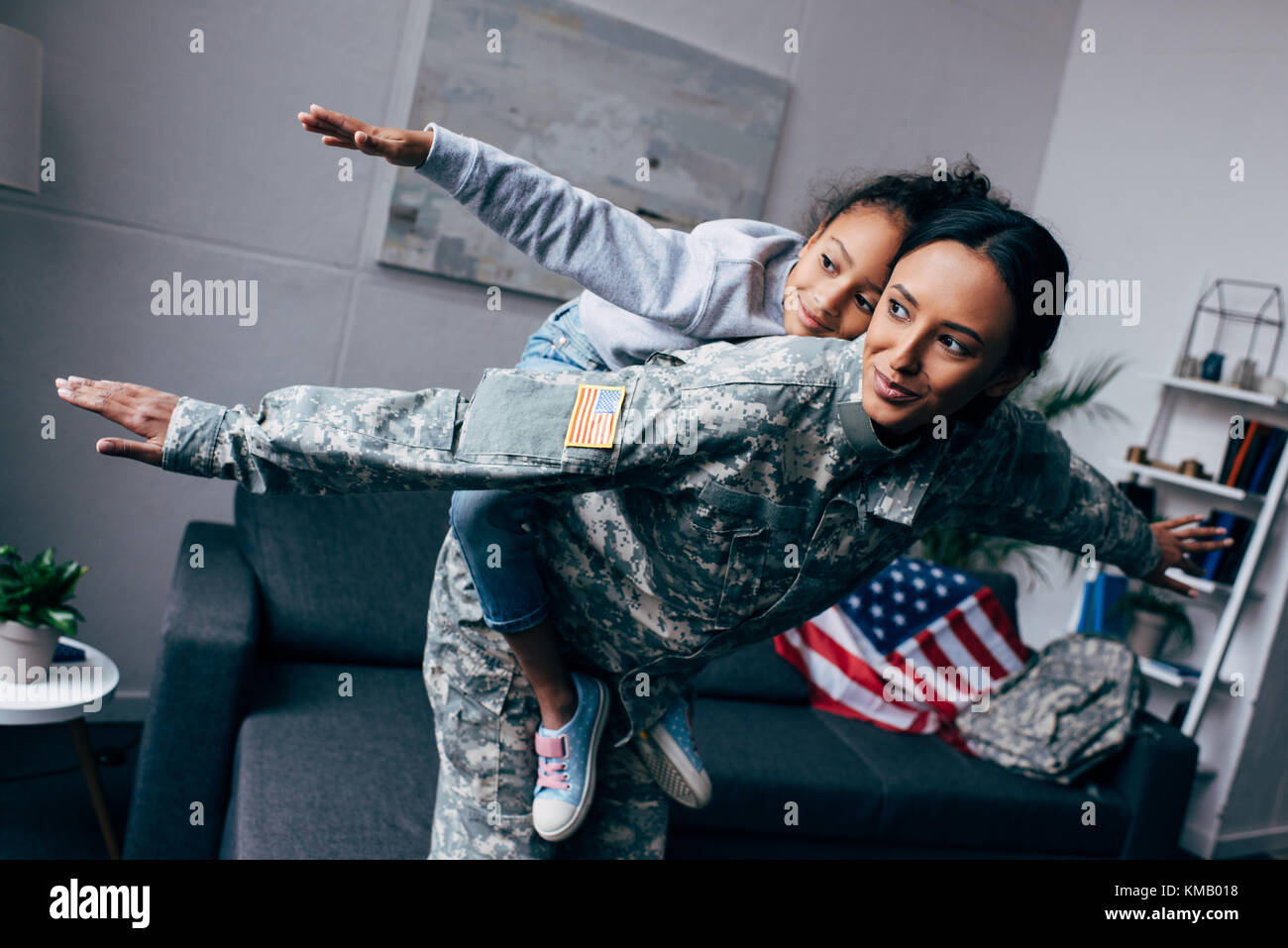 mother in military uniform piggybacking daughter - Stock Image