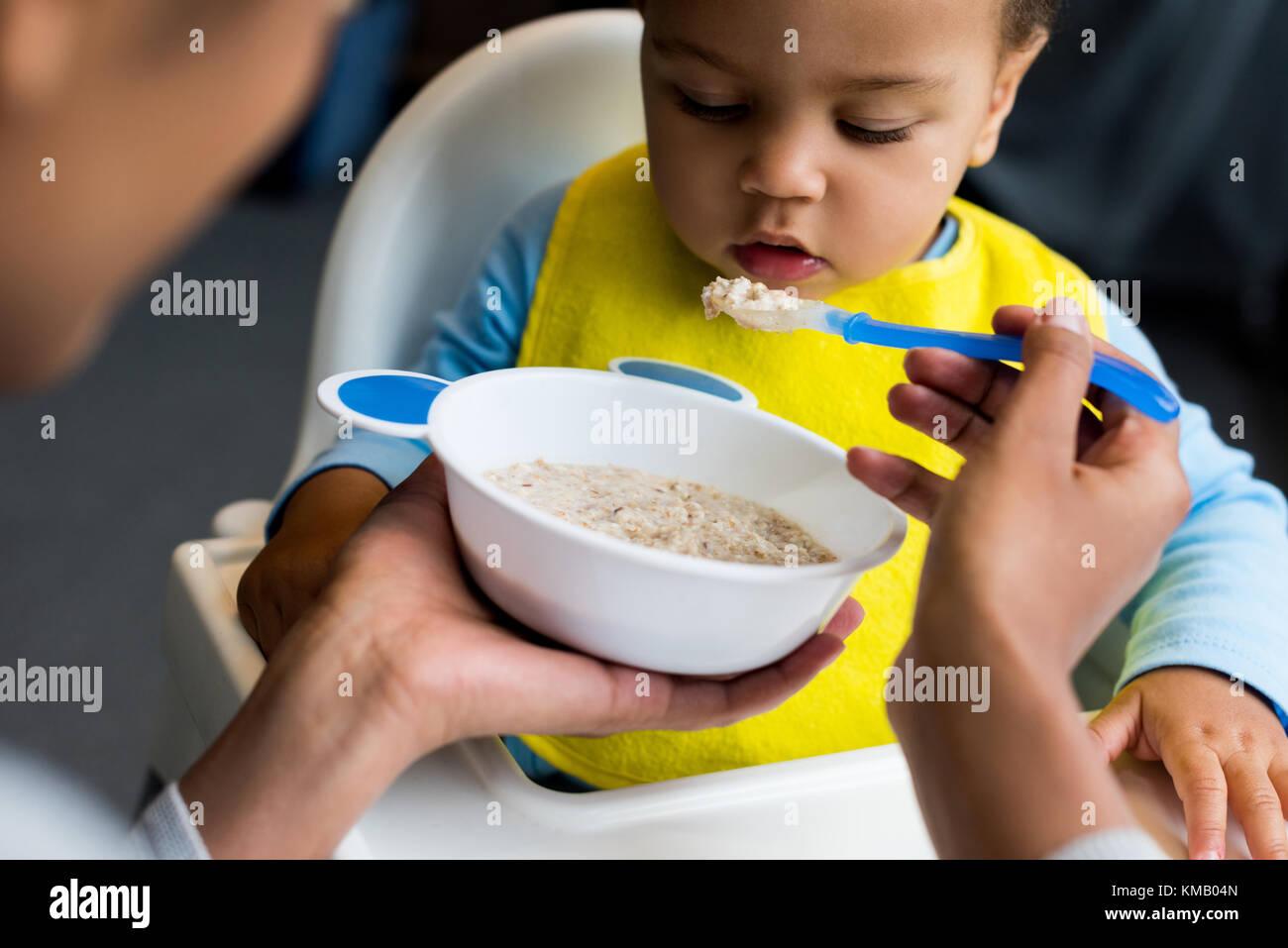 little son eating porridge - Stock Image