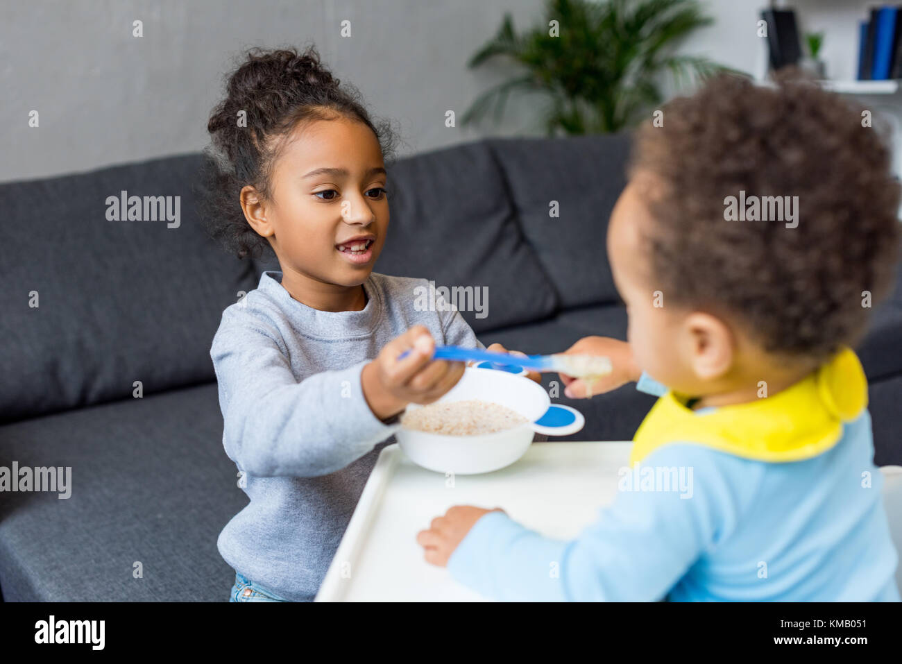 sister feeding little brother - Stock Image