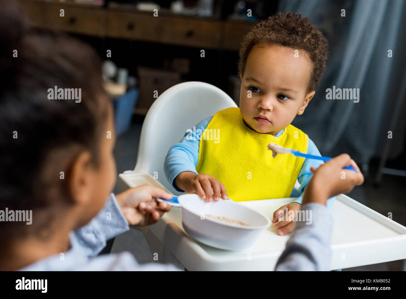 african american sister feeding brother - Stock Image
