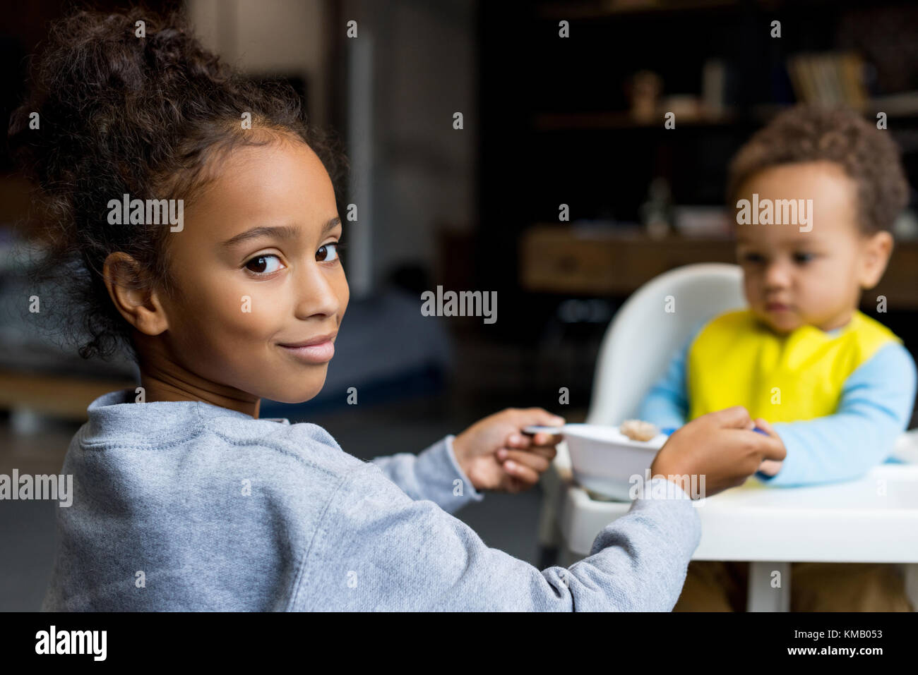 sister feeding her brother - Stock Image