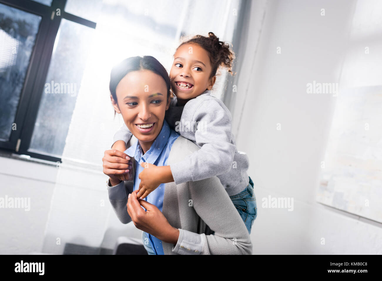 mother piggybacking her daughter - Stock Image