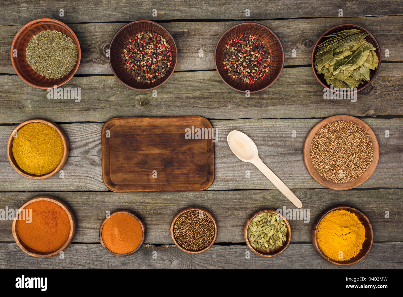 board and spoon among bowls with spices - Stock Image