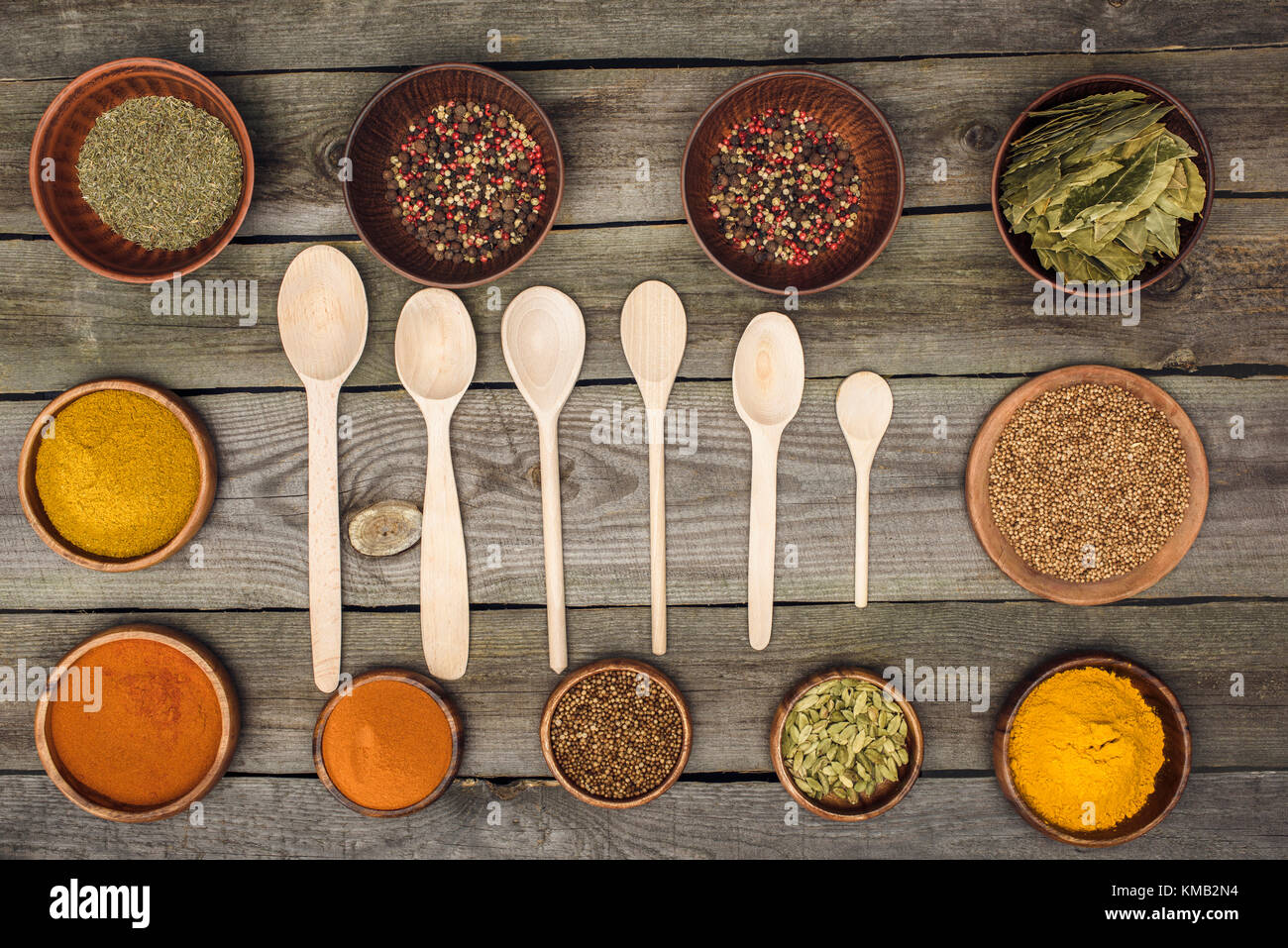 wooden spoons among bowls with spices - Stock Image