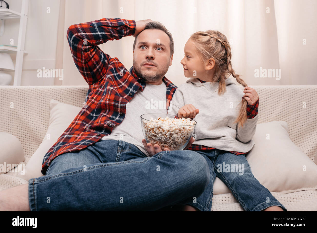 father and daughter eating popcorn - Stock Image