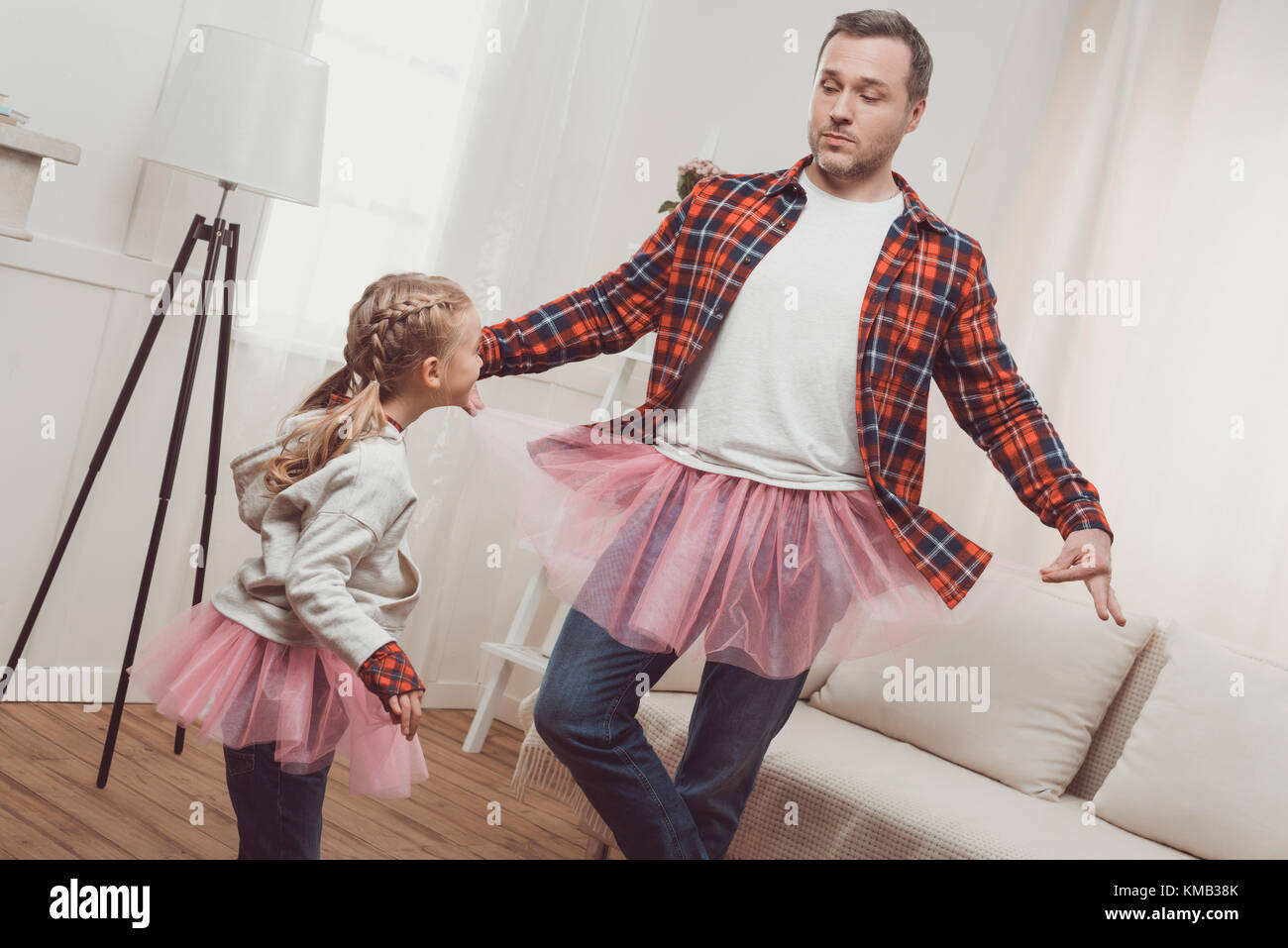 father and daughter in pink skirts - Stock Image
