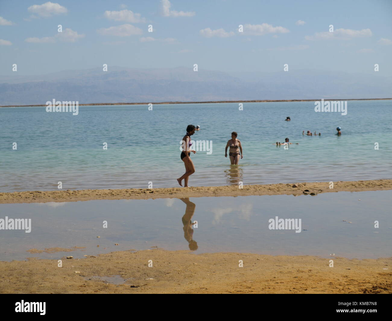 A woman with mineral mud on her face is walking on the beach of the dead sea Stock Photo