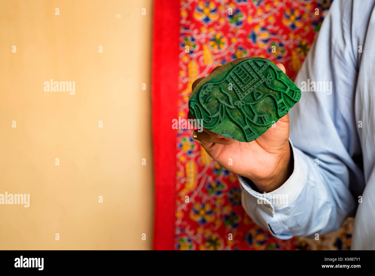 Hand holds stamp for dyeing cloth - Stock Image