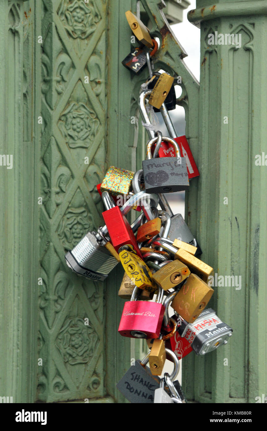 A number of colourful padlocks on a cast iron lamppost on westminster bridge in central london. Mementos and keepsakes - Stock Image