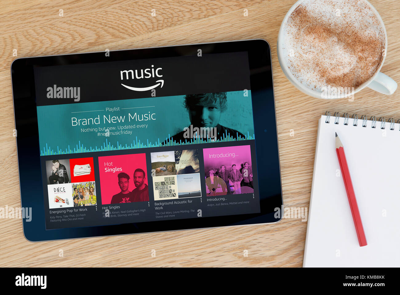 The Amazon Music app features on an iPad tablet device which rests on a wooden table beside a notepad and pencil - Stock Image