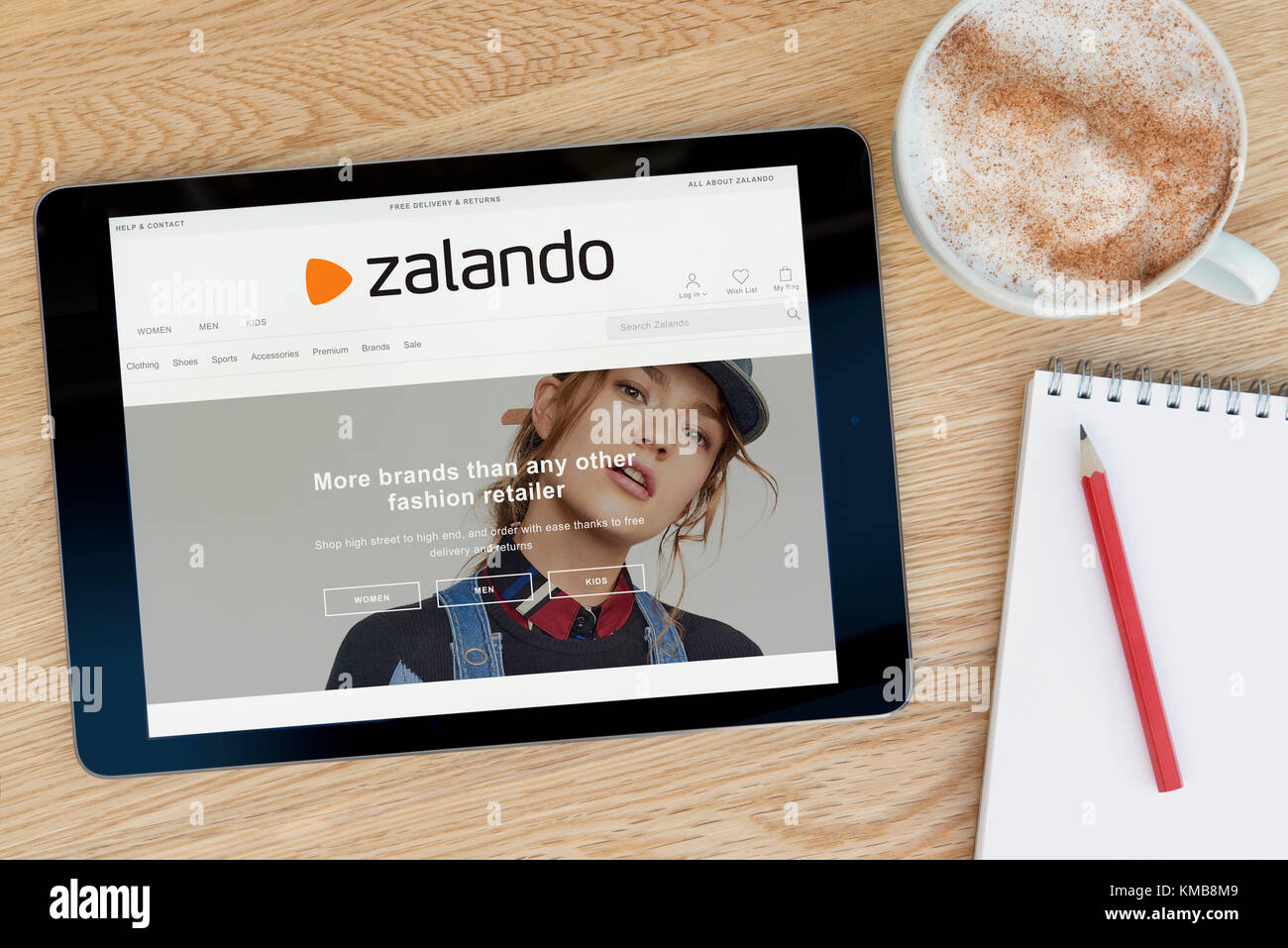 e865ed27 The Zalando website features on an iPad tablet device which rests on a  wooden table beside a notepad and pencil and a cup of coffee (Editorial  only)