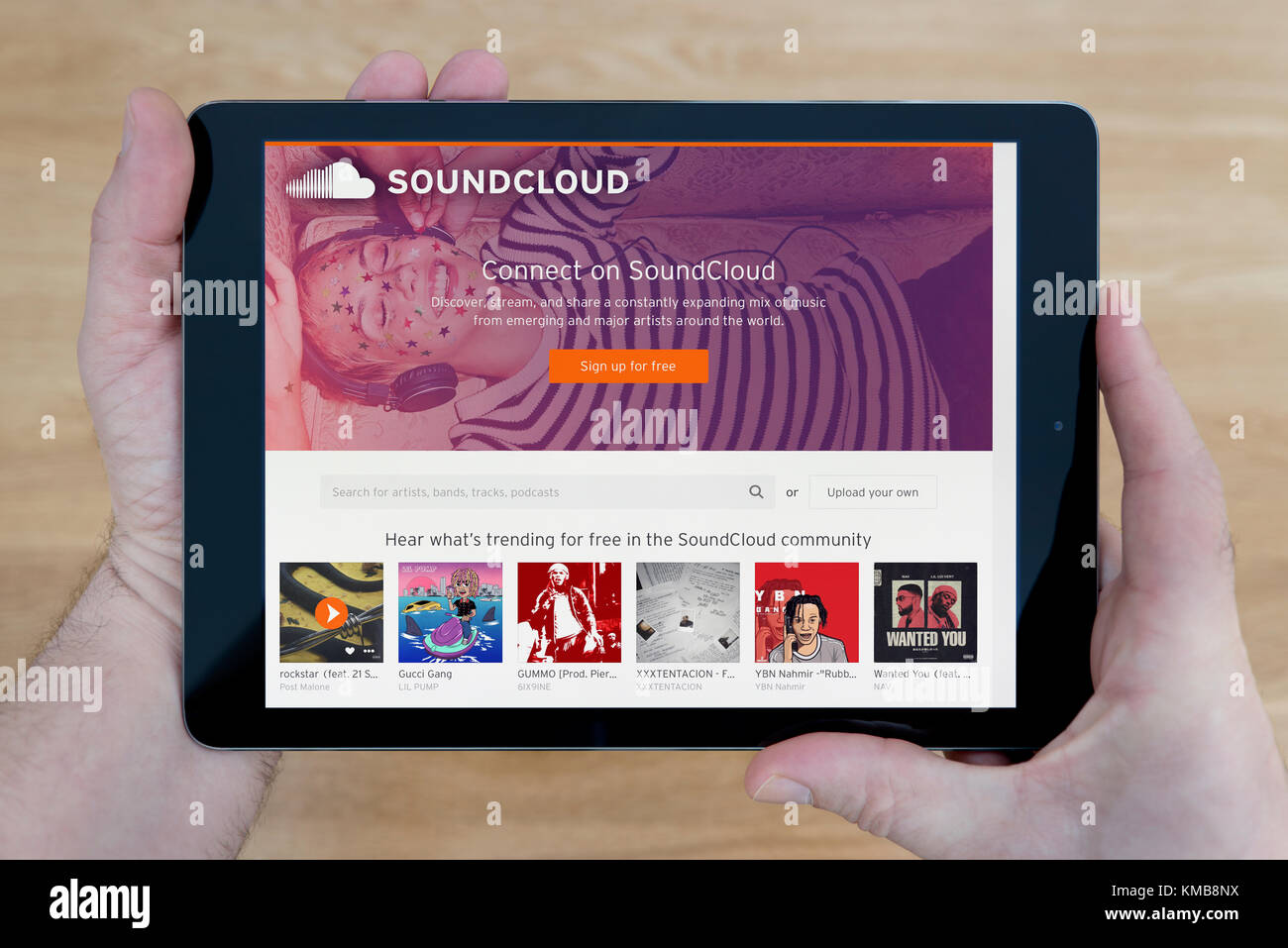 A man looks at the Soundcloud website on his iPad tablet