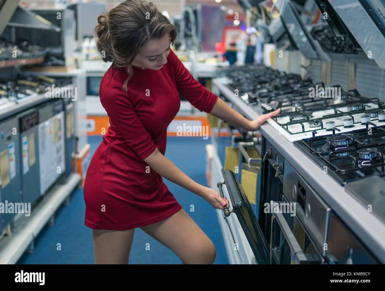 female housewife customer choosing large gas stove - Stock Image