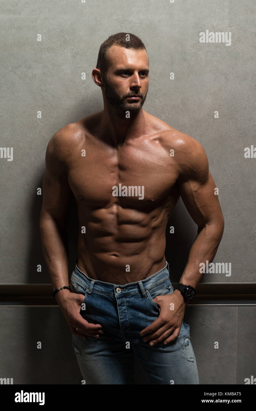 7873c9e3 Healthy Young Man Standing Strong Standing Against a Wall and Flexing  Muscles While Wearing Blue Jeans - Muscular Athletic Bodybuilder Fitness  Model P