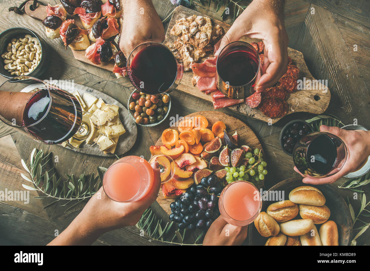 People having party sitting at table set with wine snacks - Stock Image