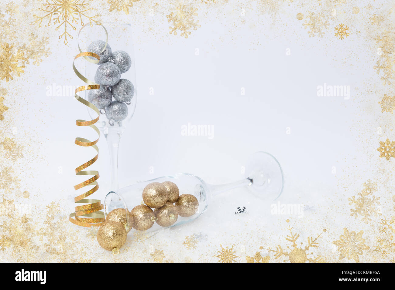 creative new year celebration concept with champagne glasses on fake snow and golden tinsel stock