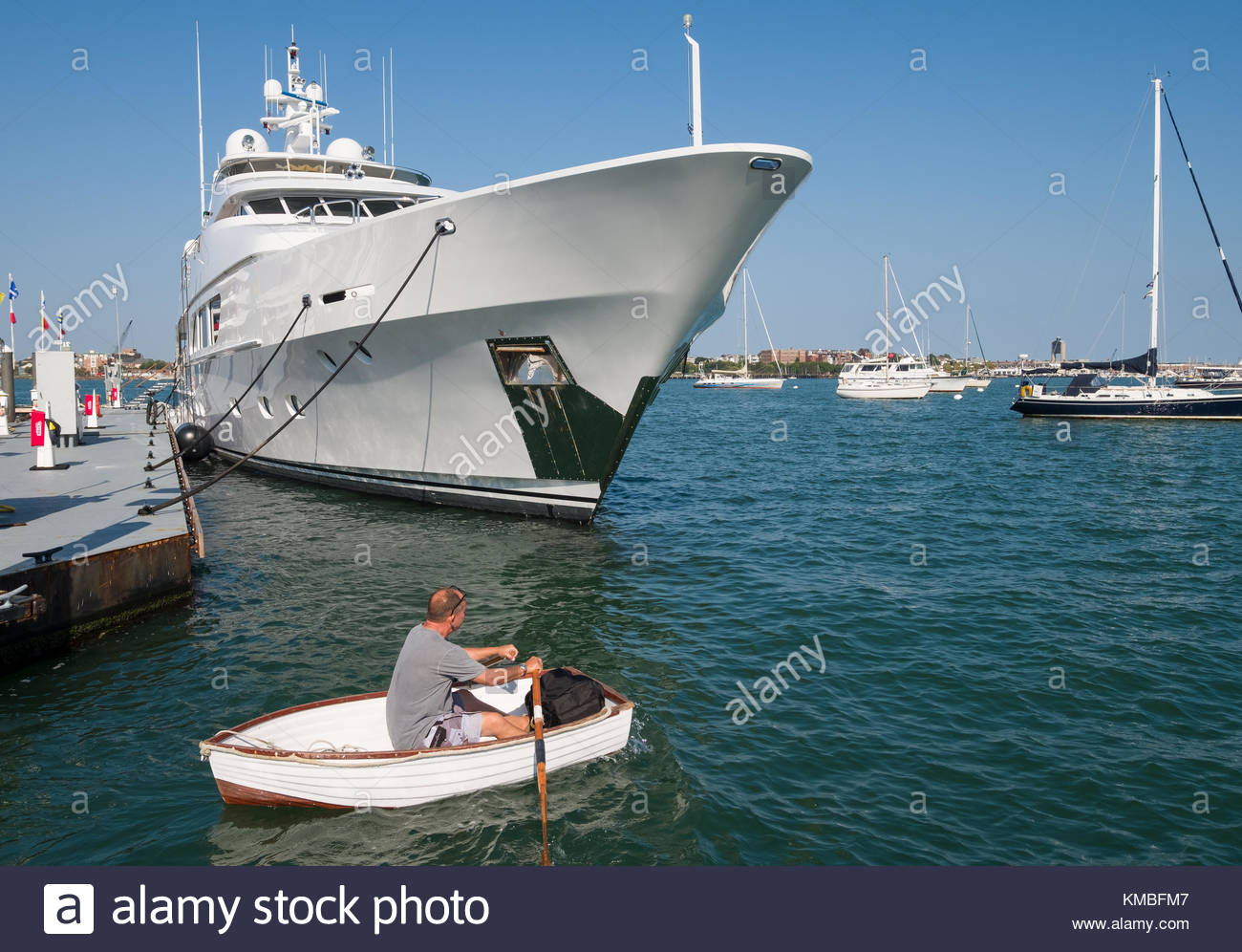 Man rowing small dinghy past mega luxury yacht moored to floating pier in the Boston Waterboat Marina, North Atlantic - Stock Image