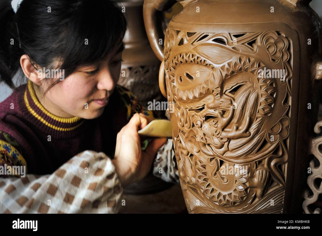 Traditional Longshan Chinese black pottery. Artist finishing vase before firing in production studio near Jinan, - Stock Image