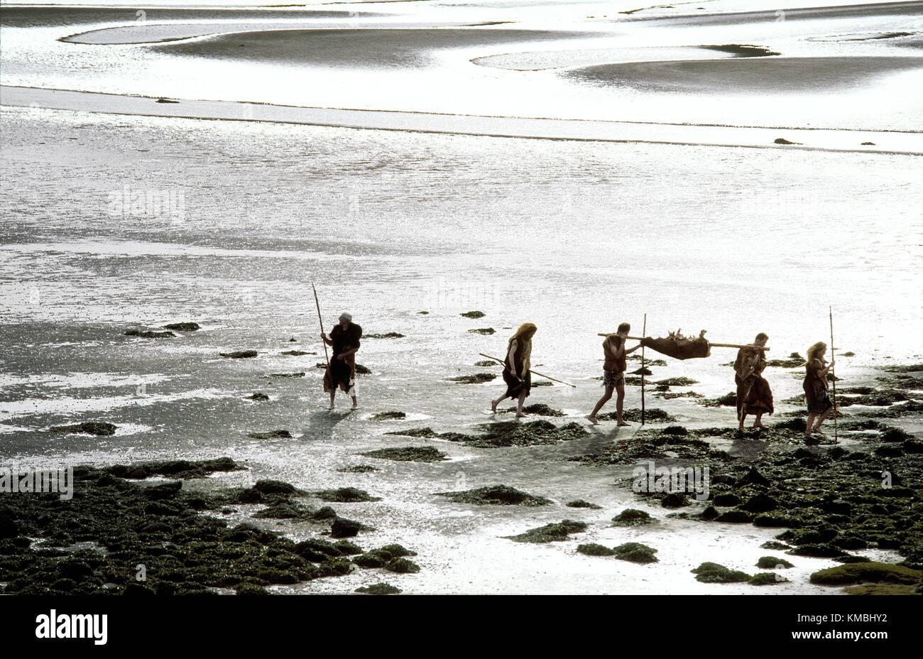 Neolithic prehistoric cave men caveman cavemen cave man walking on mud flat tidal estuary carrying deer food carcass - Stock Image