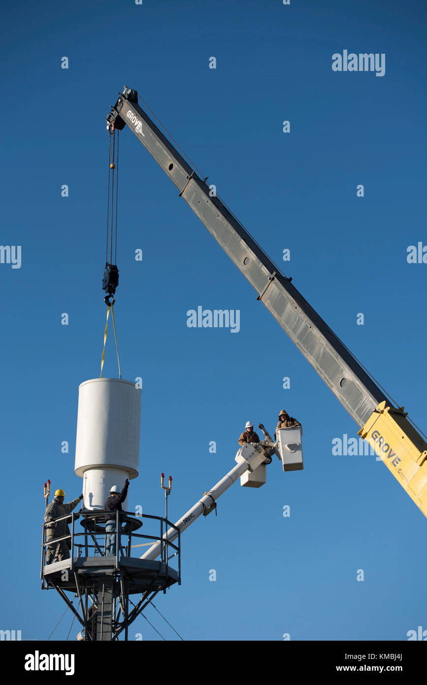 Airmen and contractors guide Offutt Air Force Base's (AFB) legacy Tactical Air Navigation System (TACAN) as a crane - Stock Image