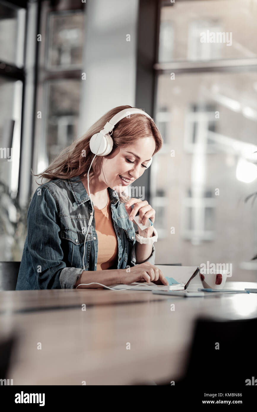 Positive young woman looking at her notes and smiling - Stock Image