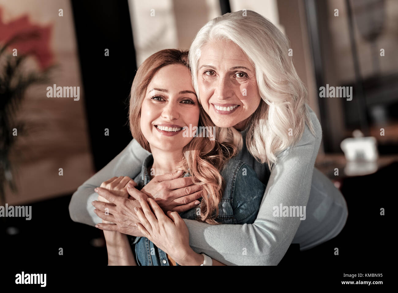 Happy senior woman hugging her positive granddaughter in a cafe - Stock Image