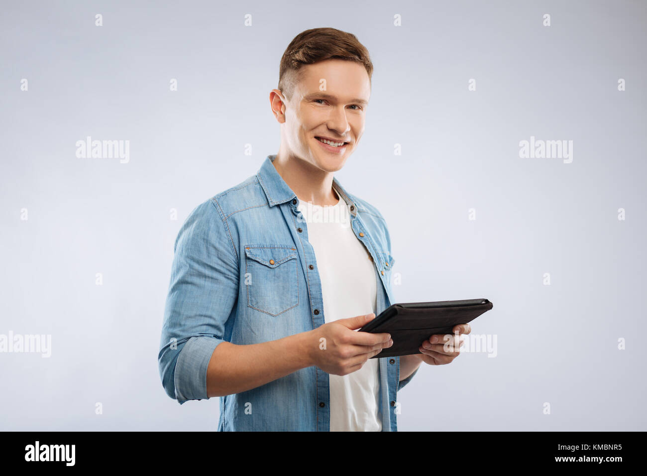 Handsome man holding his gadget - Stock Image