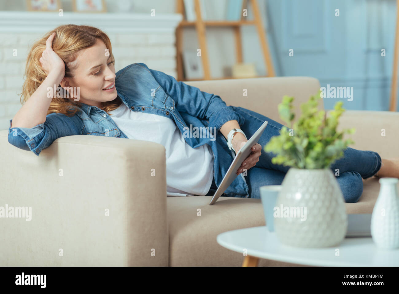 Positive relaxing woman reading a book on a tablet and smiling - Stock Image