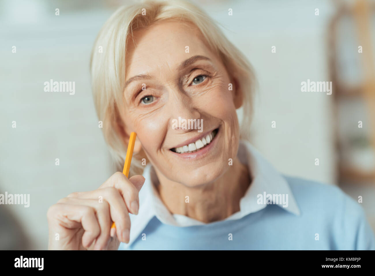 Positive pensioner smiling while holding a yellow pencil - Stock Image