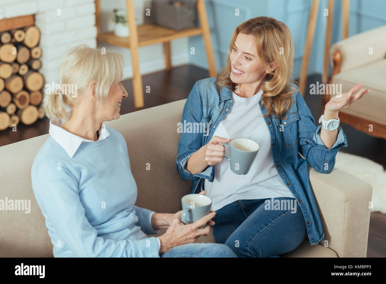 Senior woman and her kind granddaughter telling each other interesting stories - Stock Image