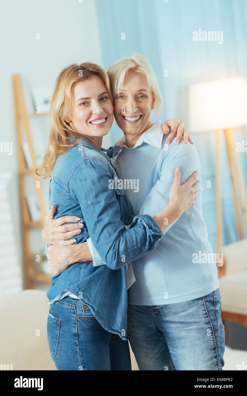 Cheerful relatives standing and hugging after a long journey - Stock Image