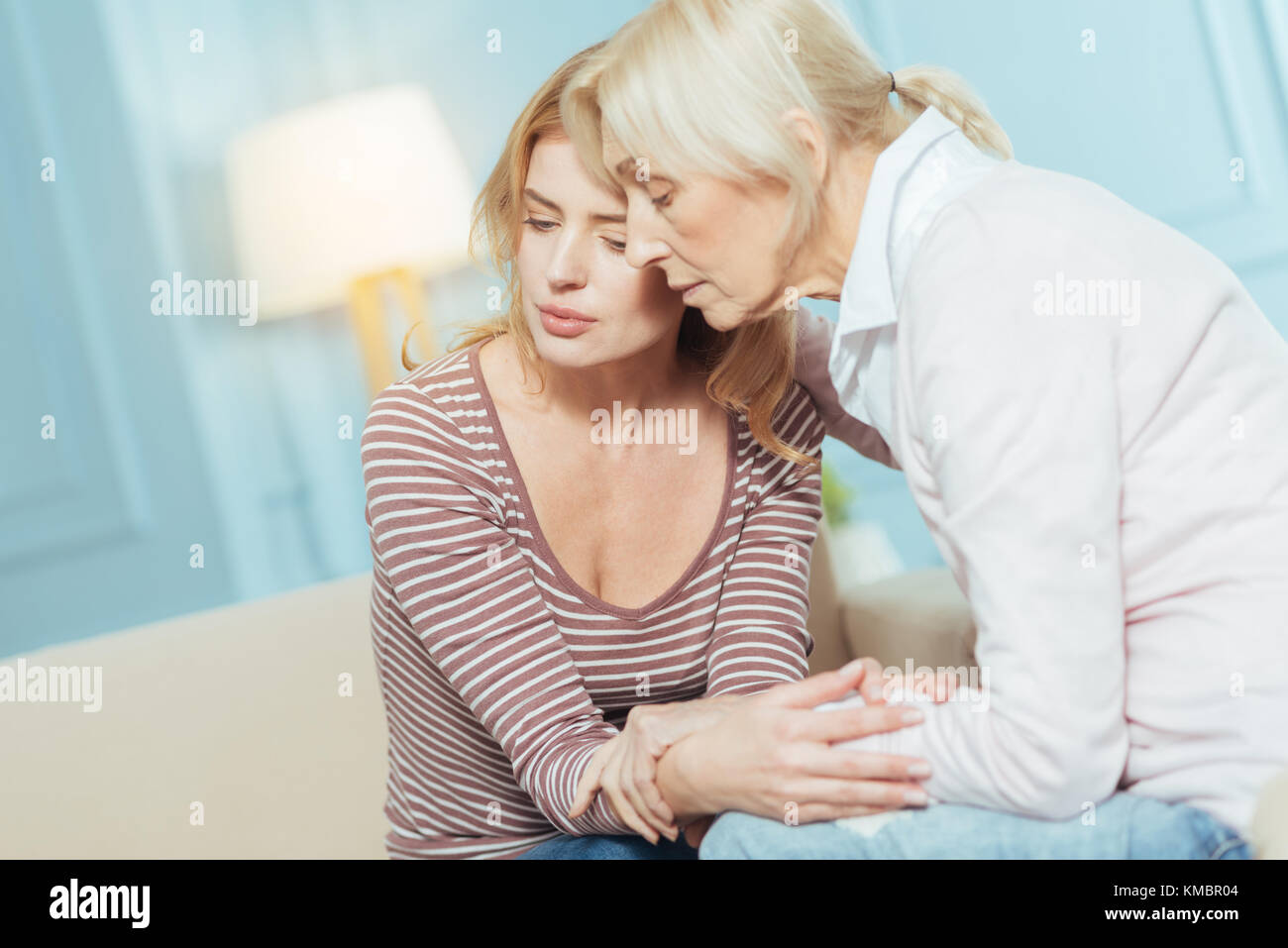 Kind attentive pensioner hugging and supporting her granddaughter - Stock Image