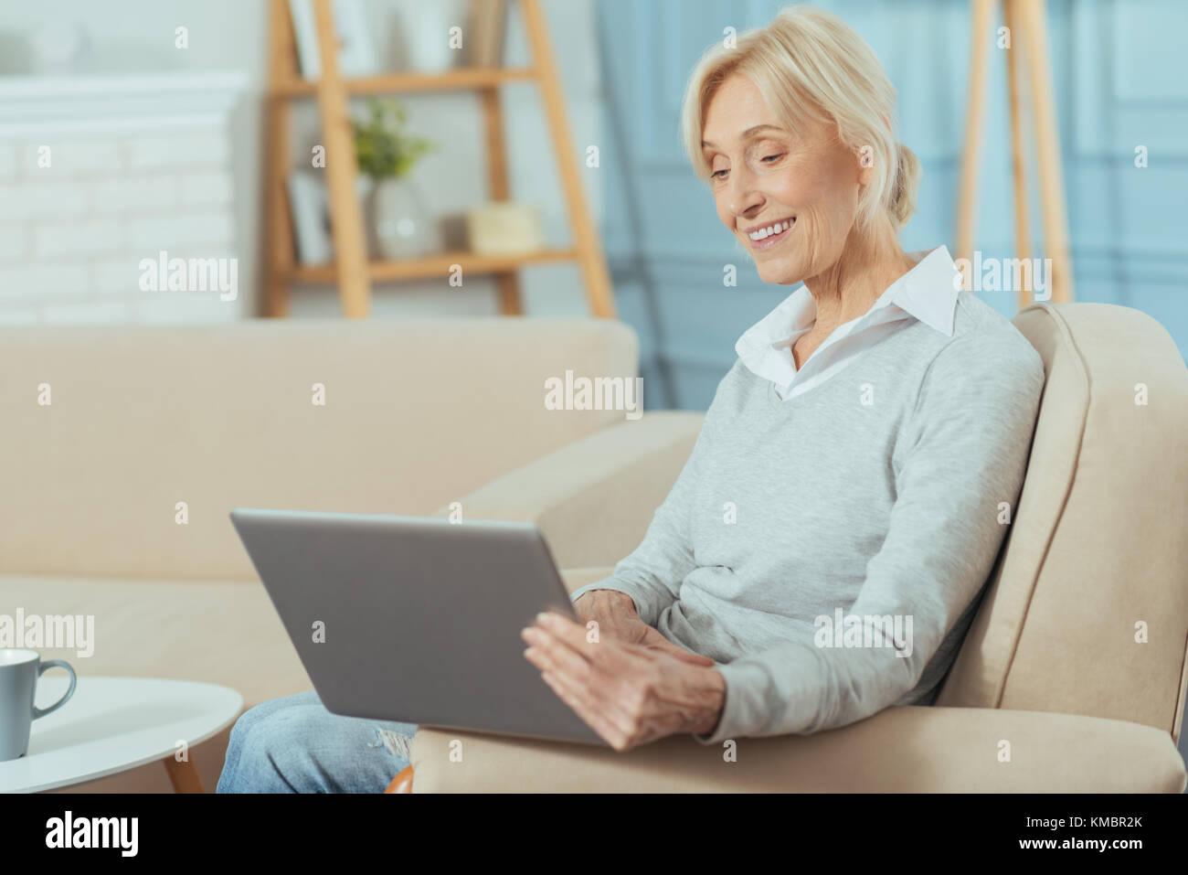 Progressive senior woman enjoying her new laptop and smiling - Stock Image