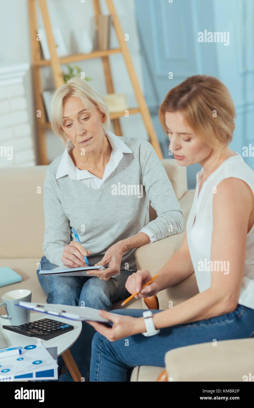 Smart financial advisor explaining everything and showing the documents - Stock Image