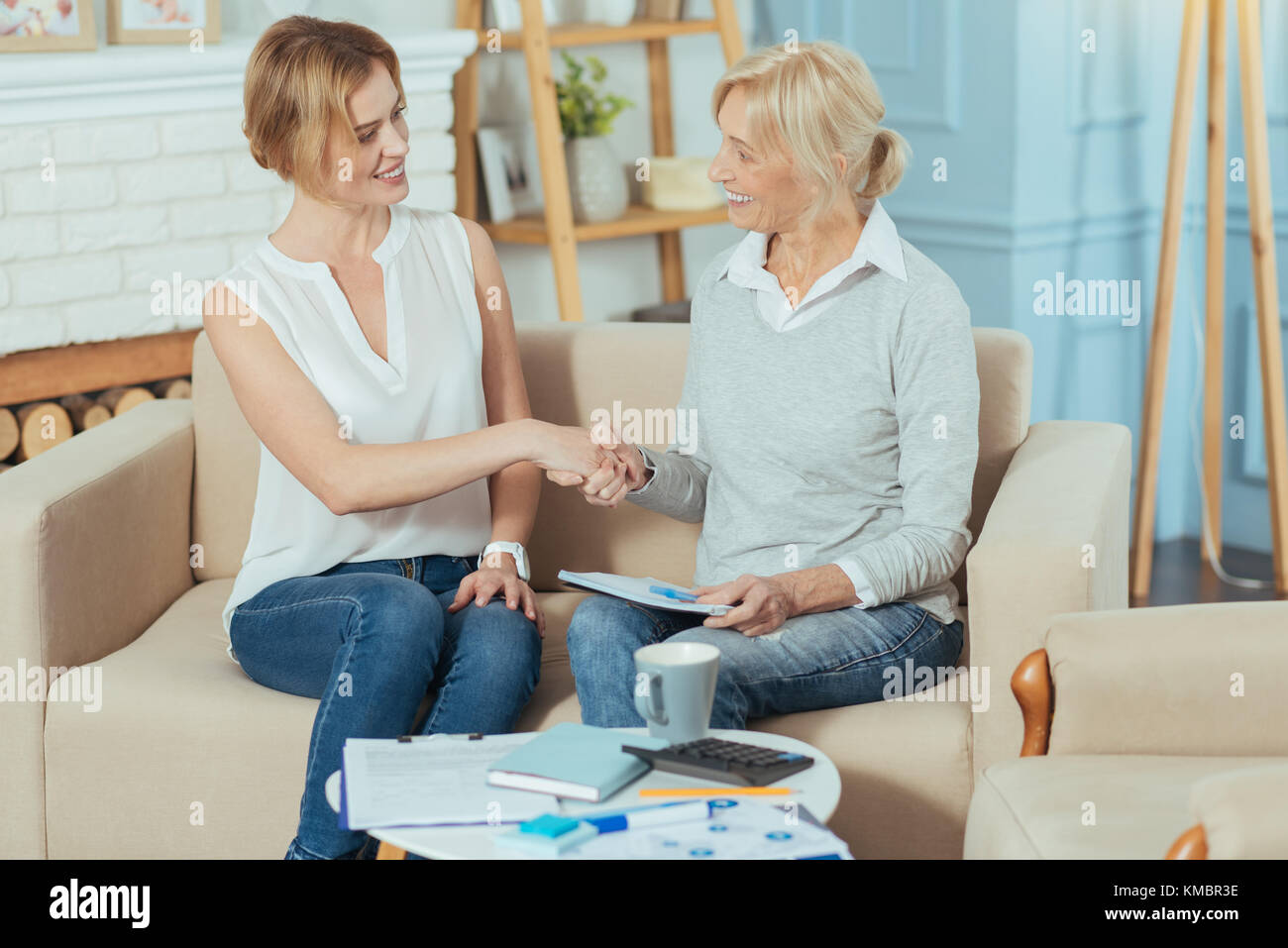 Smiling pensioner having a deal with her clever financial advisor - Stock Image