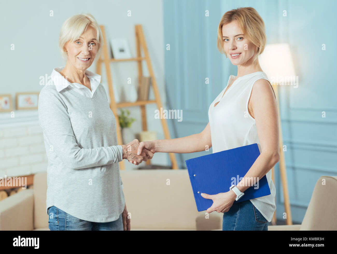 Smart financial advisor shaking hands with her grateful client and smiling - Stock Image