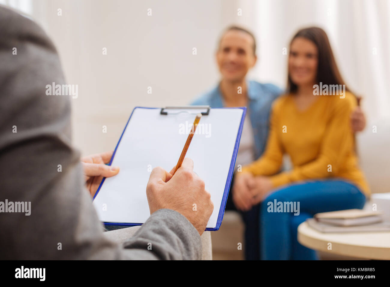 Psychologist writing down thoughts during therapy - Stock Image