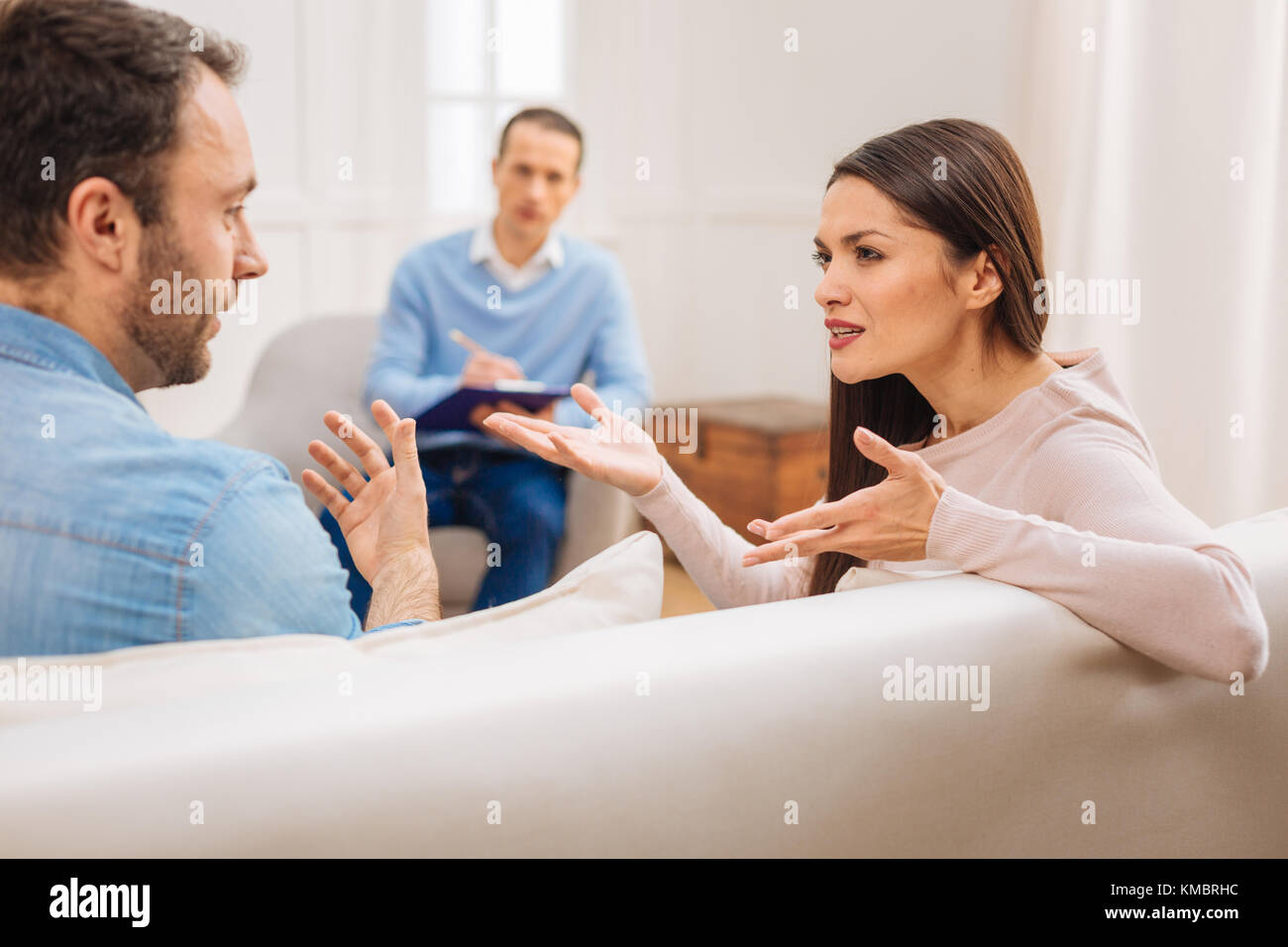 Angry elegant wife shows dissatisfaction to husband during therapy - Stock Image
