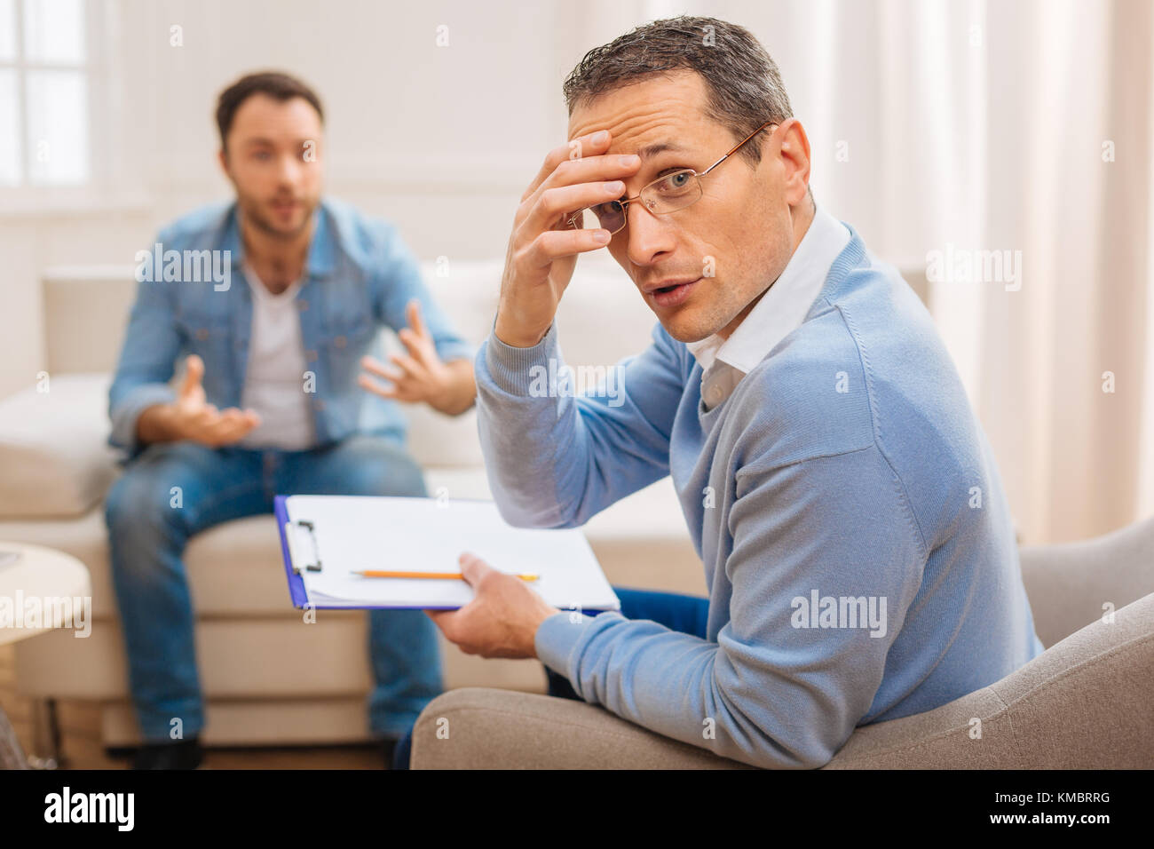 Tired amazed psychologist conducting therapy  - Stock Image
