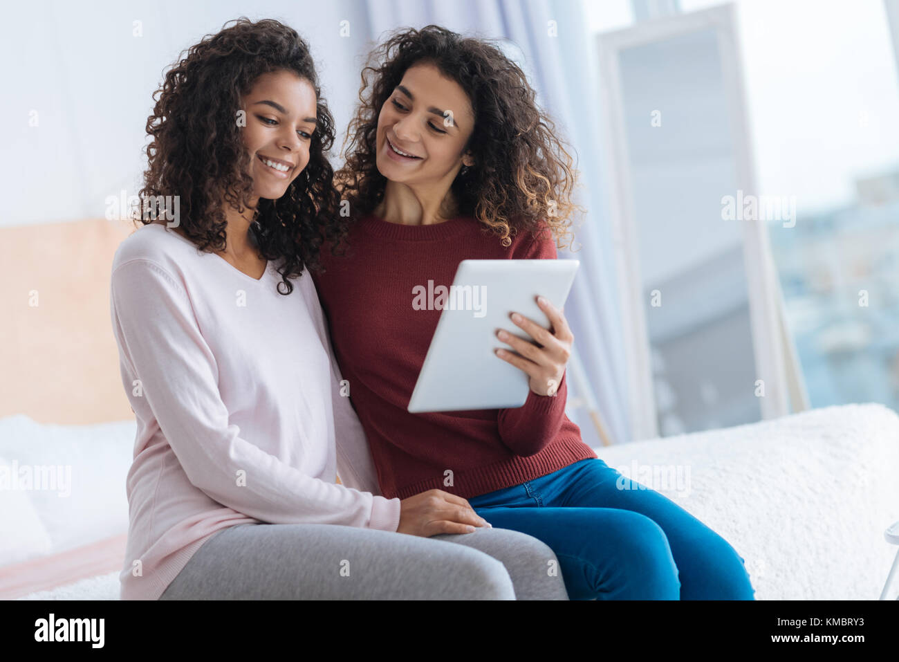 Curious young lady holding touchpad and smiling to her sister - Stock Image